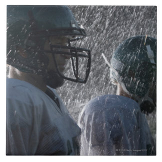 Two American football players in rain, side view Tile