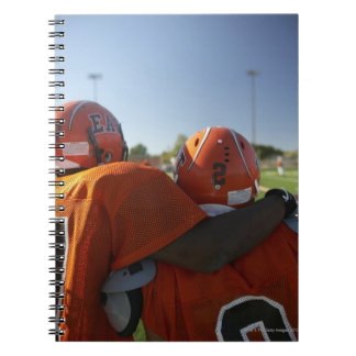 Two American football players looking at playing Notebook