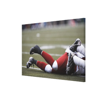 Two American football players lying on field, Canvas Print