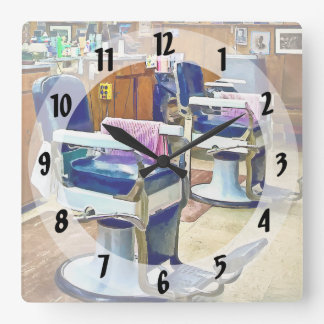 Two Barber Chairs With Pink Striped Barber Capes Square Wall Clock