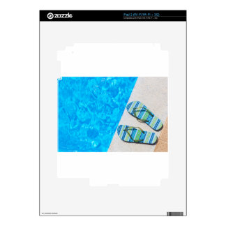 Two bathing slippers on edge of swimming pool iPad 2 skins