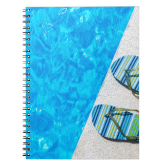 Two bathing slippers on edge of swimming pool notebook