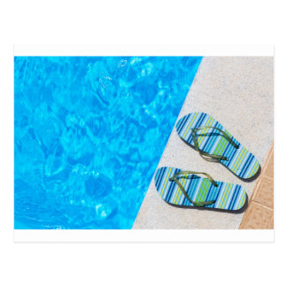 Two bathing slippers on edge of swimming pool postcard