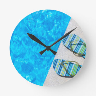 Two bathing slippers on edge of swimming pool round clock