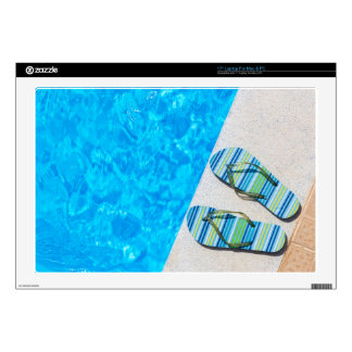 Two bathing slippers on edge of swimming pool skin for laptop