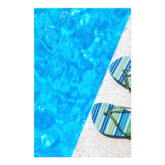 Two bathing slippers on edge of swimming pool stationery