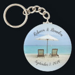 "Two Beach Chairs Custom Wedding Key Ring Favors<br><div class=""desc"">Wedding key ring favors with two beach chairs in the sand and custom text. Personalize with names at the top and wedding date at the bottom. Bulk order discounts apply when buying this type of key chain. Empty chairs beneath a white umbrella look out over turquoise ocean water. This is...</div>"