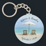 """Two Beach Chairs Custom Wedding Key Ring Favors<br><div class=""""desc"""">Wedding key ring favors with two beach chairs in the sand and custom text. Personalize with names at the top and wedding date at the bottom. Bulk order discounts apply when buying this type of key chain. Empty chairs beneath a white umbrella look out over turquoise ocean water. This is...</div>"""
