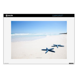 "Two blue starfish at water's edge on tropical 2 decal for 15"" laptop"