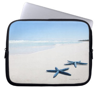 Two blue starfish at water's edge on tropical 2 laptop sleeve