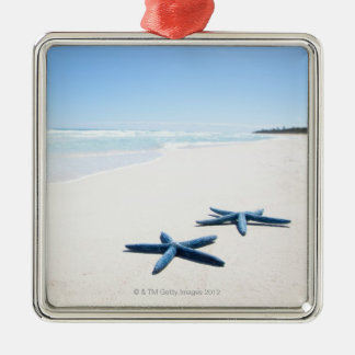 Two blue starfish at water's edge on tropical 2 square metal christmas ornament