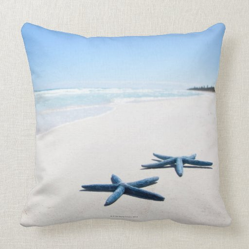 Two blue starfish at water's edge on tropical 2 throw pillows
