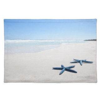 Two blue starfish at water's edge on tropical 2 place mat