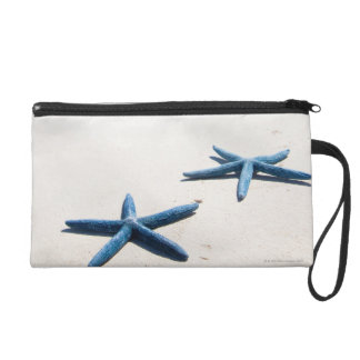 Two blue starfish at water's edge on tropical wristlet purse