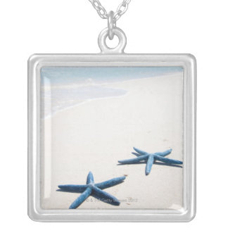 Two blue starfish at water's edge on tropical silver plated necklace