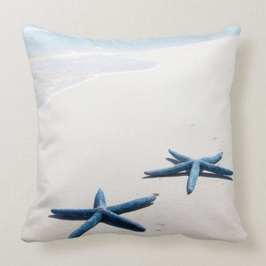 Two blue starfish at water's edge on tropical throw pillow