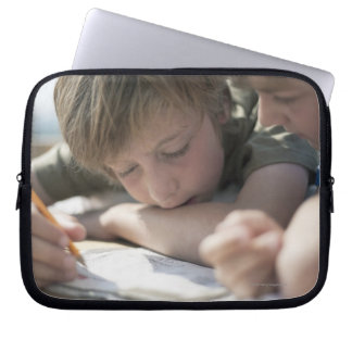 Two boys writing together laptop sleeves