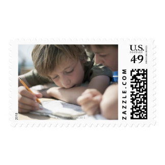 Two boys writing together postage