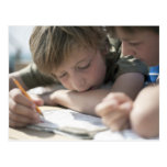Two boys writing together postcards