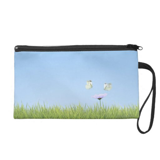 Two butterflies hovering over flower wristlet purse
