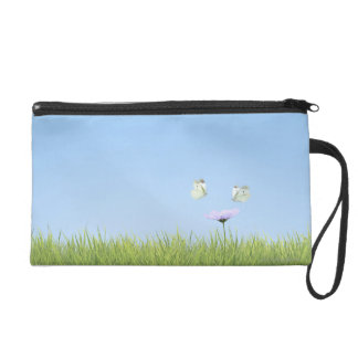 Two butterflies hovering over flower wristlets