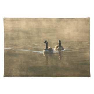 two canada geese swimming on the river by sunrise placemat