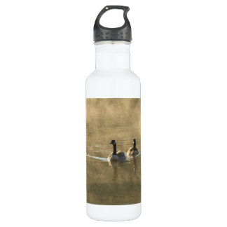 two canada geese swimming on the river by sunrise water bottle