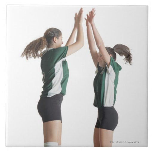 two caucasian female volleyball players from the large square tile