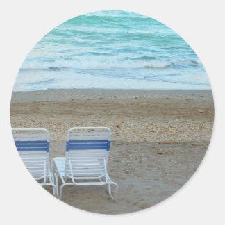 Two chairs on beach sand ocean waves round sticker