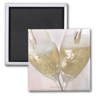 Two champagne flutes being filled with sparkling magnet