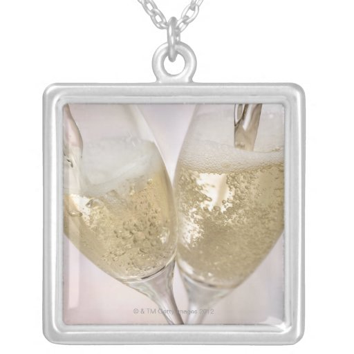 Two champagne flutes being filled with sparkling necklace