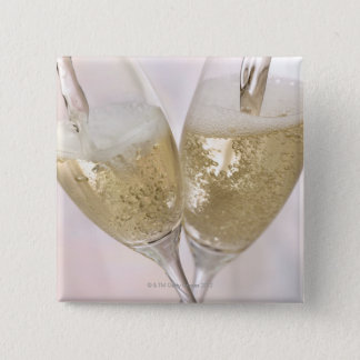 Two champagne flutes being filled with sparkling pinback button