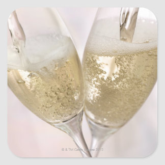 Two champagne flutes being filled with sparkling square sticker