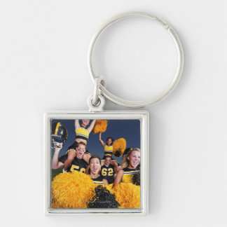 Two cheerleaders riding on shoulders of football keychain