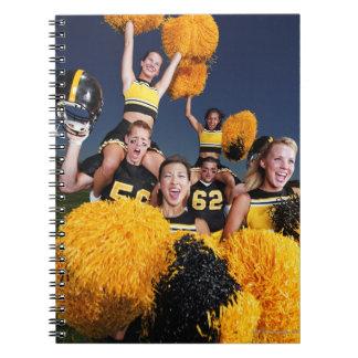 Two cheerleaders riding on shoulders of football notebook