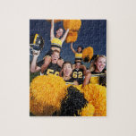 Two cheerleaders riding on shoulders of football puzzle