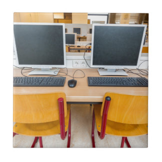 Two computers in classroom on high school tile