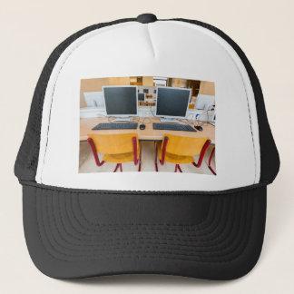 Two computers in classroom on high school trucker hat