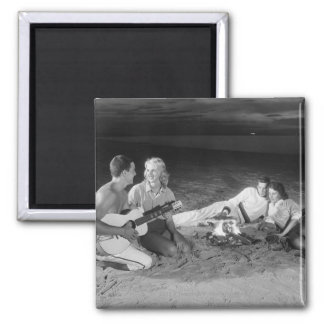 Two couples on beach sitting around campfire magnet