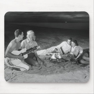 Two couples on beach sitting around campfire mouse pad