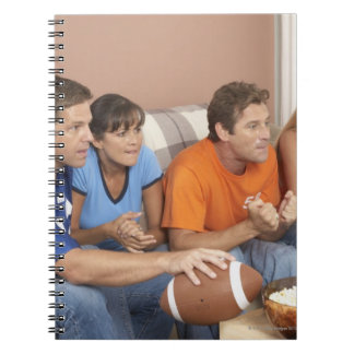 Two couples watching football in living room notebook
