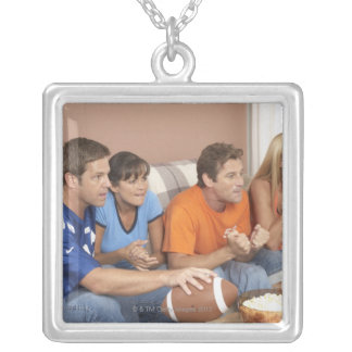 Two couples watching football in living room square pendant necklace