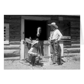 Two cowboys standing next to a barn with a horse card