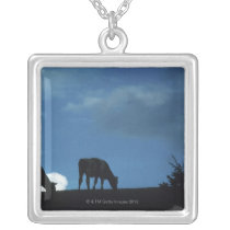 Two cows in silhouette grazing on hillside silver plated necklace
