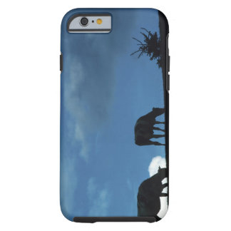 Two cows in silhouette grazing on hillside tough iPhone 6 case