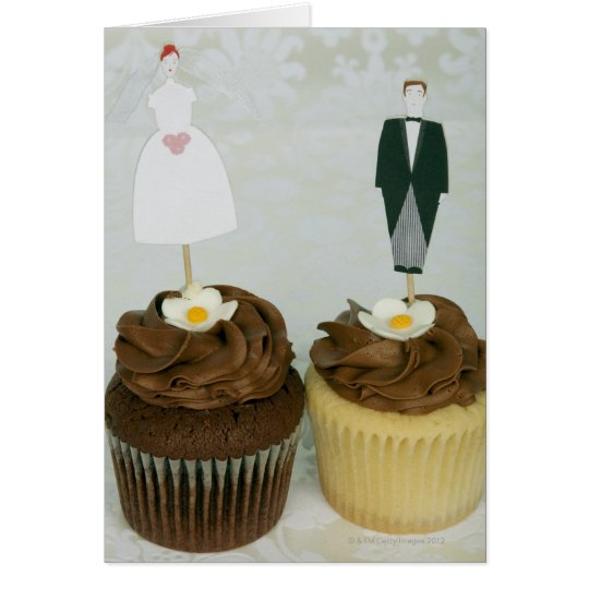 Two cupcakes with toy bride and groom on them card