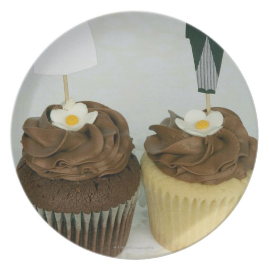 Two cupcakes with toy bride and groom on them dinner plate