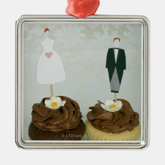 Two cupcakes with toy bride and groom on them metal ornament