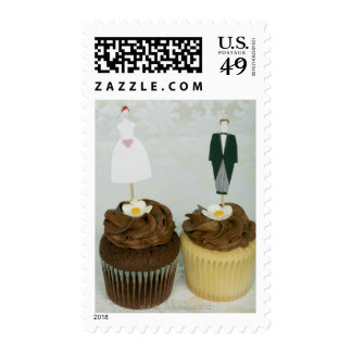 Two cupcakes with toy bride and groom on them postage stamp