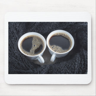 Two cups of coffee wrapped a black wool scarf mouse pad